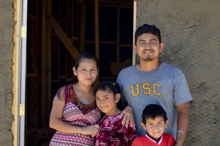 Elias and Rebeca with their children in front of their new house