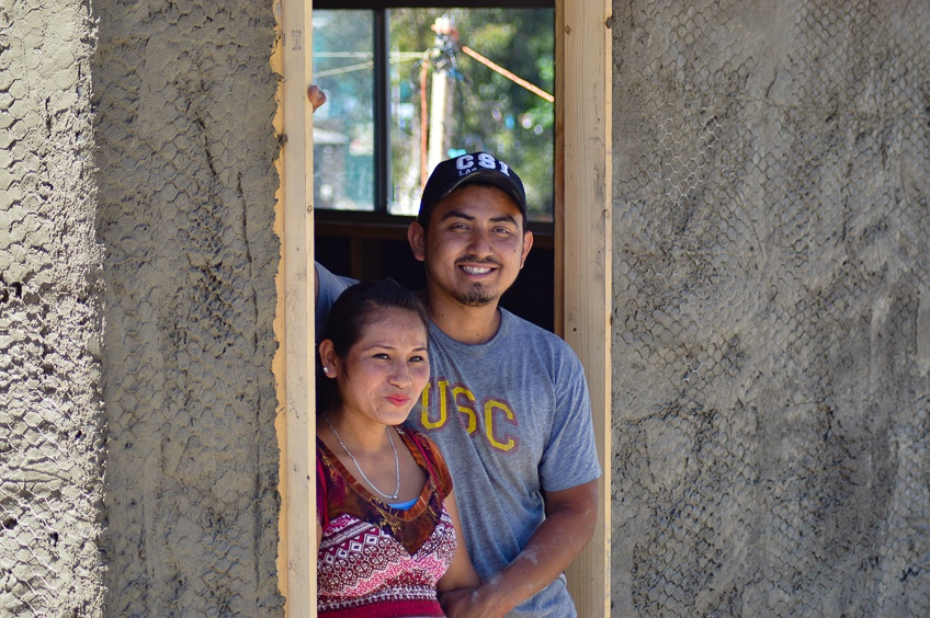 smiling couple in front of their new home
