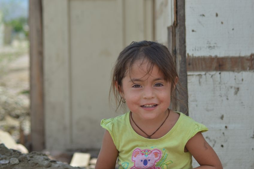 Mexican_girl_in_front_of_her_old_house